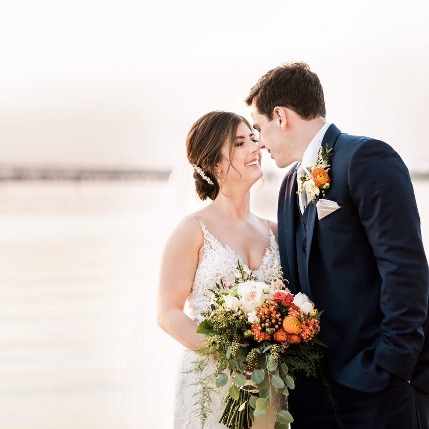 bride and groom pose in front of bay bridge