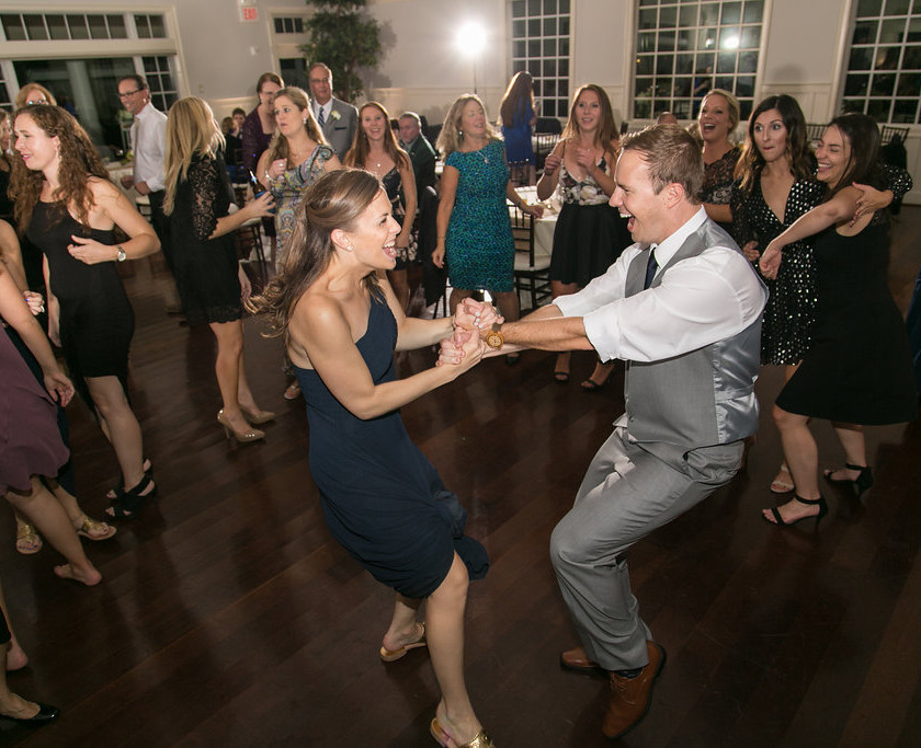 groomsman and woman spin around on dance floor