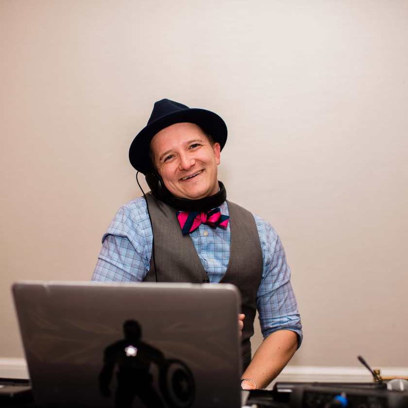 dj playing music and smiling while wearing hat and bowtie