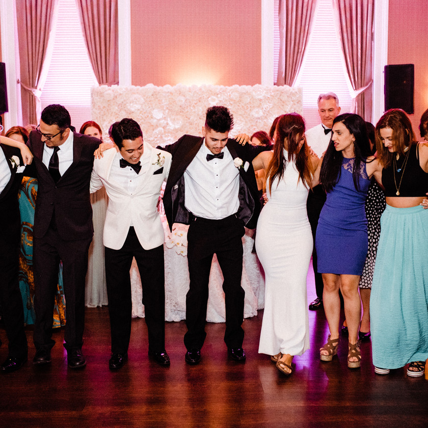groom and family arm in arm around dance floor