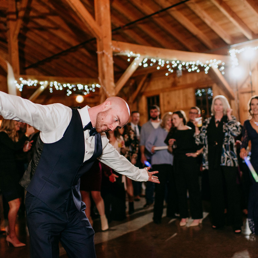 groomsman dancing while surrounded by guests