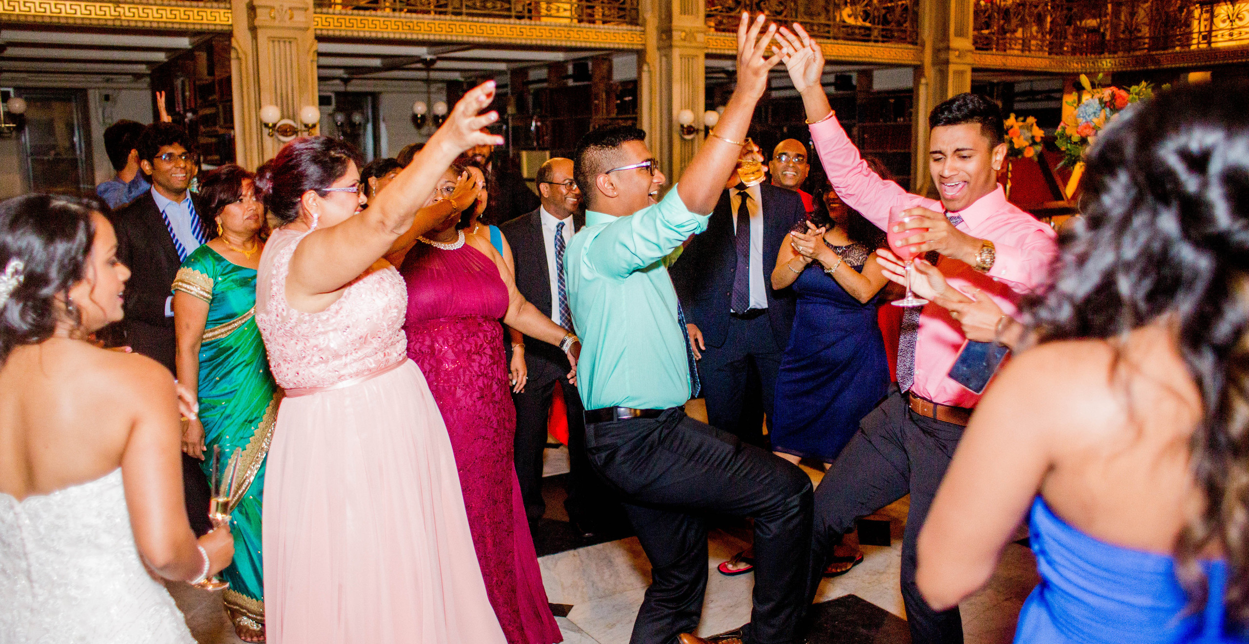 two guys dance at center of group at wedding