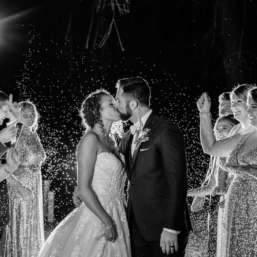 bride and groom kiss during confetti exit