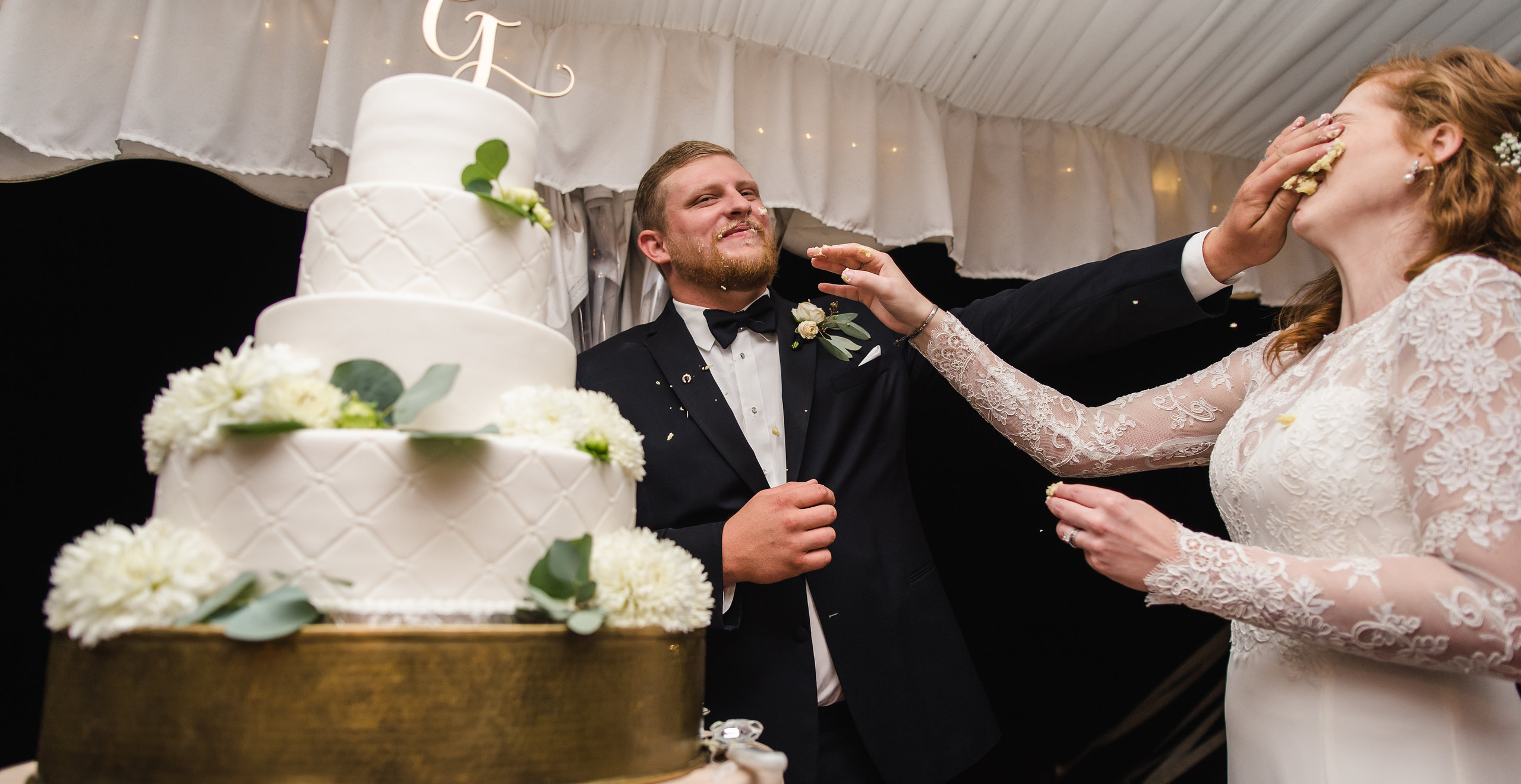 bride and groom smash cake into each other's faces