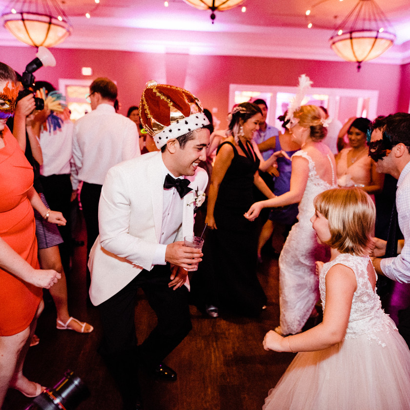 groom dancing with young girl and wedding guests