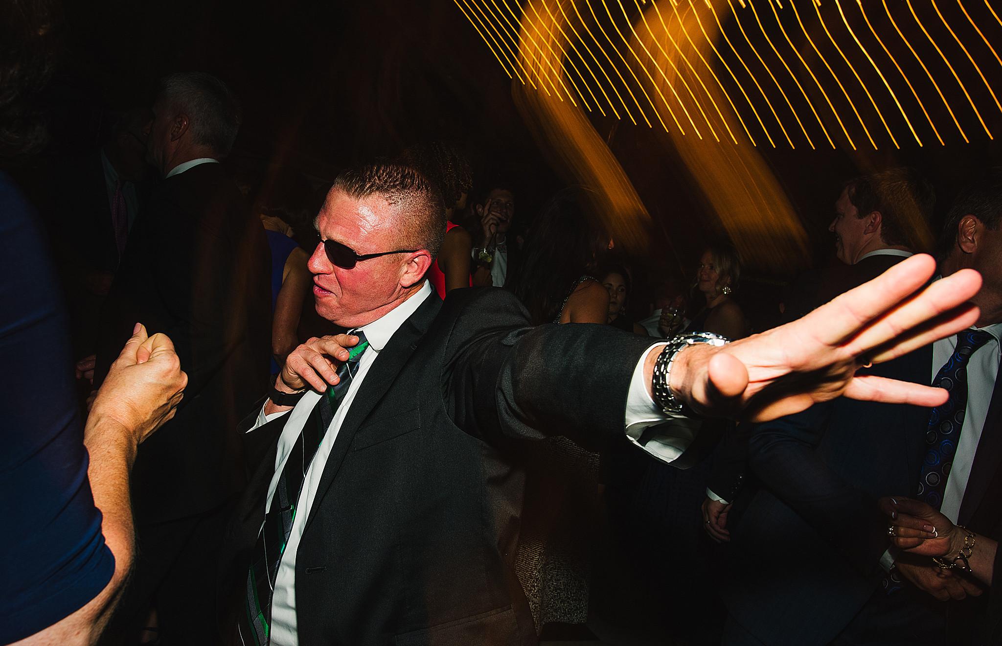 man with sunglasses dances at wedding