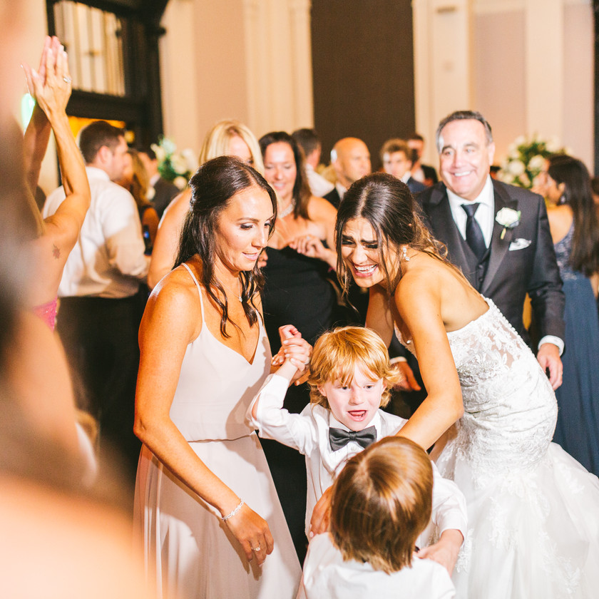 bride smiles while dancing with young boys