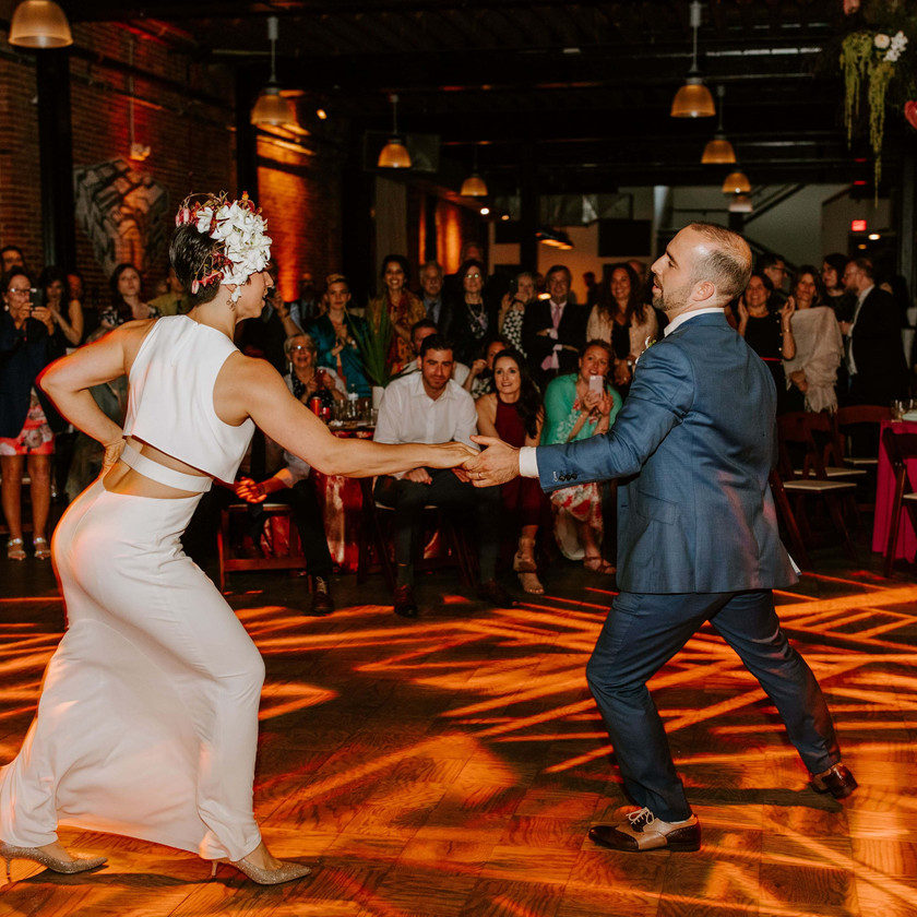 bride and groom first dance with guests watching