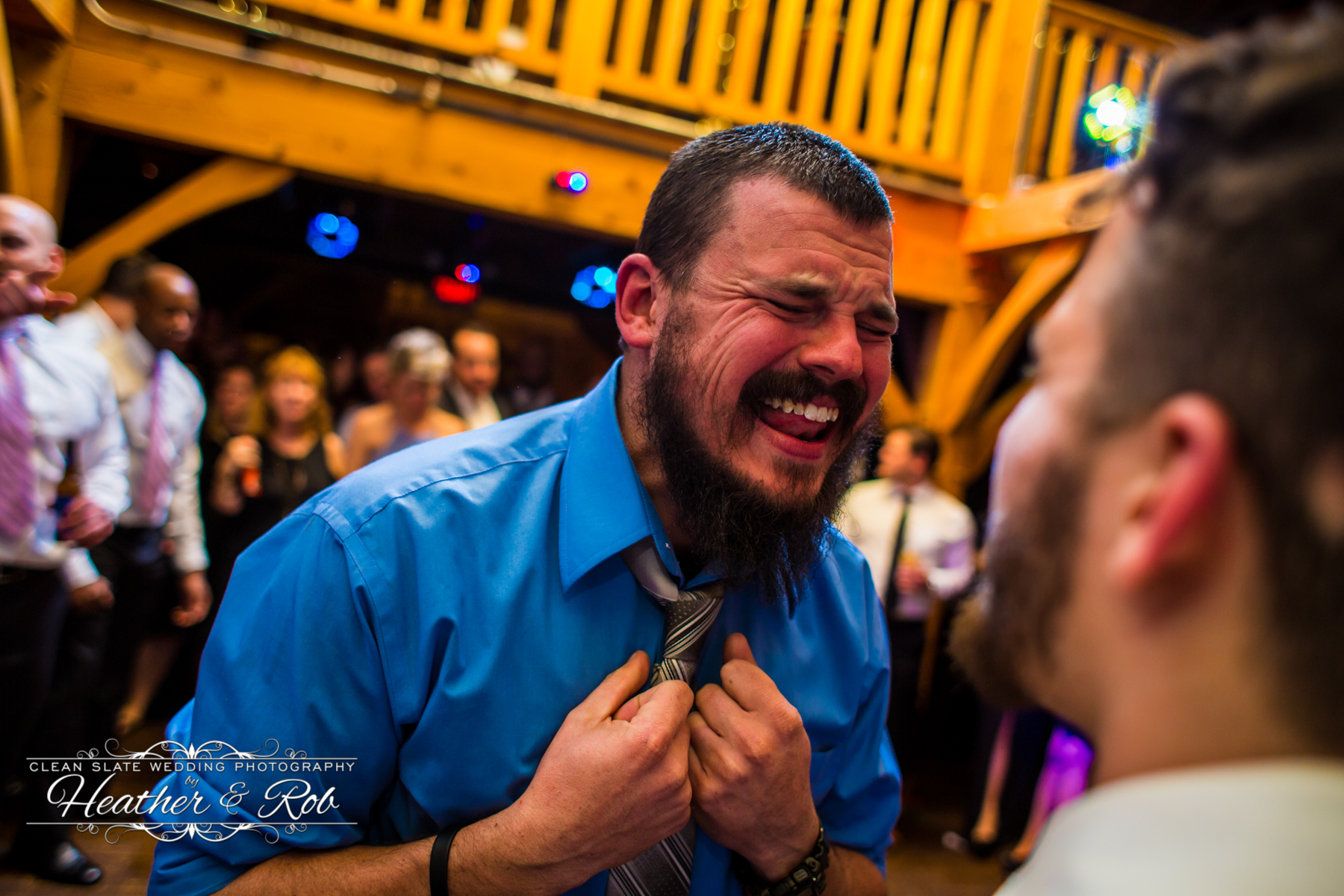 man in blue shirt singing with eyes closed on dance floor at wedding