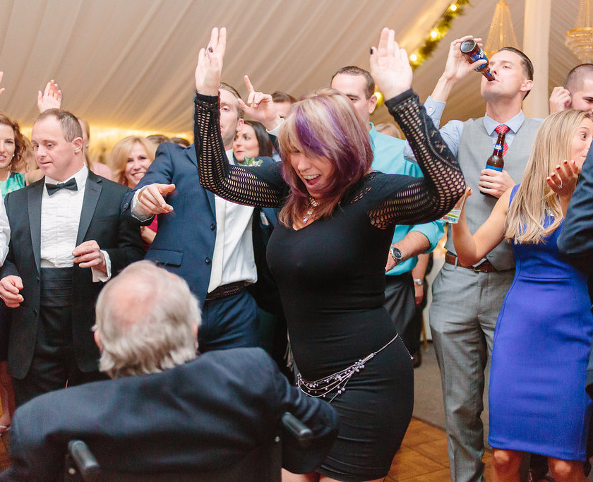 woman in black dress dancing with hands up
