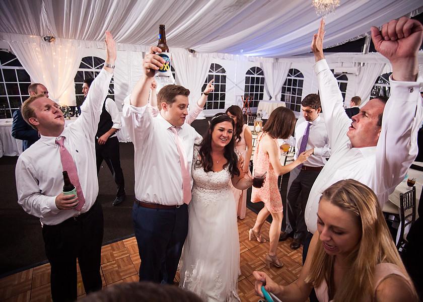 bride, groom, and guests dance