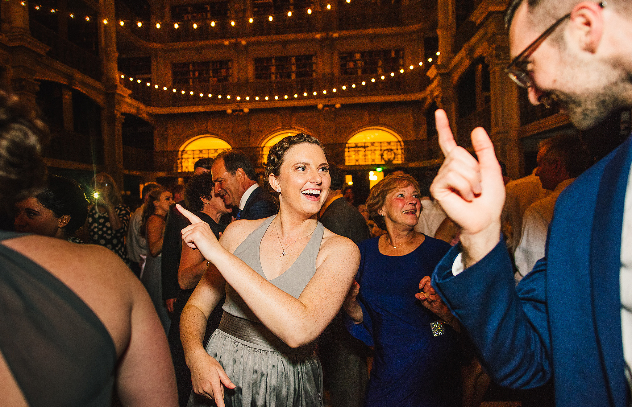 woman in grey dress dances at wedding