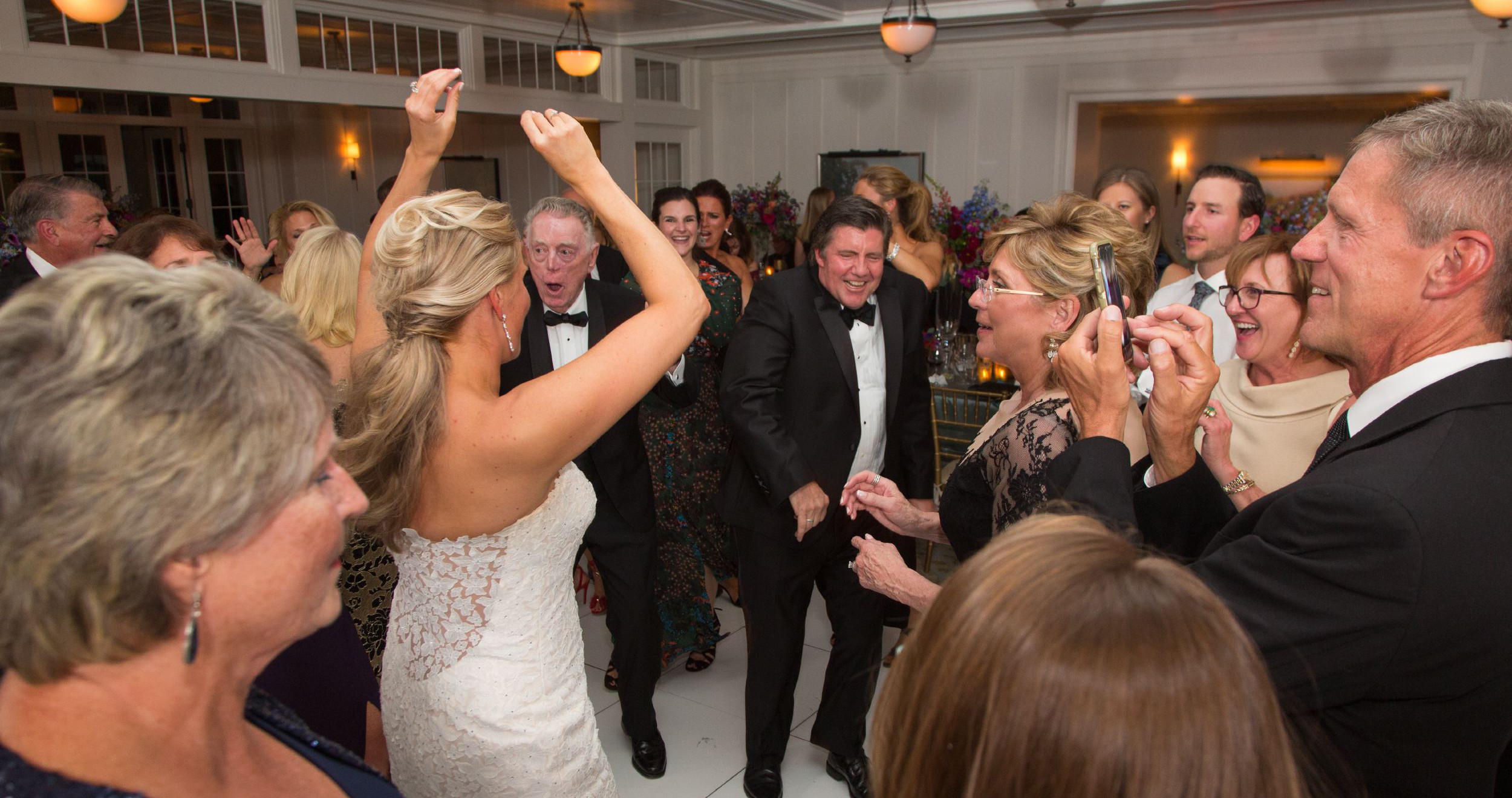bride dancing with hands up surrounded by guests