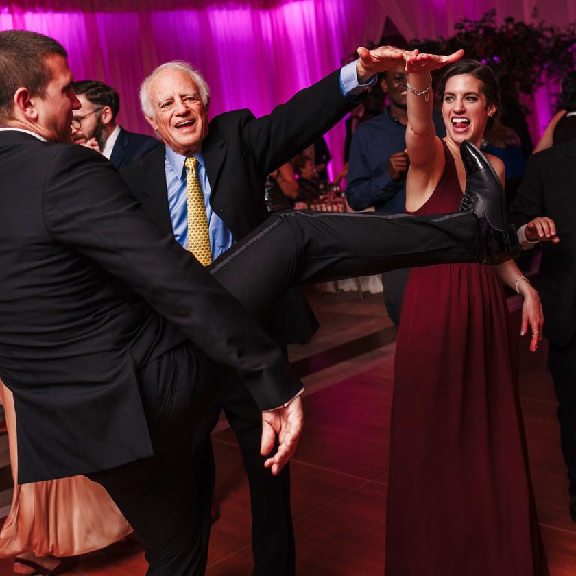 guy does high kick while dancing at wedding