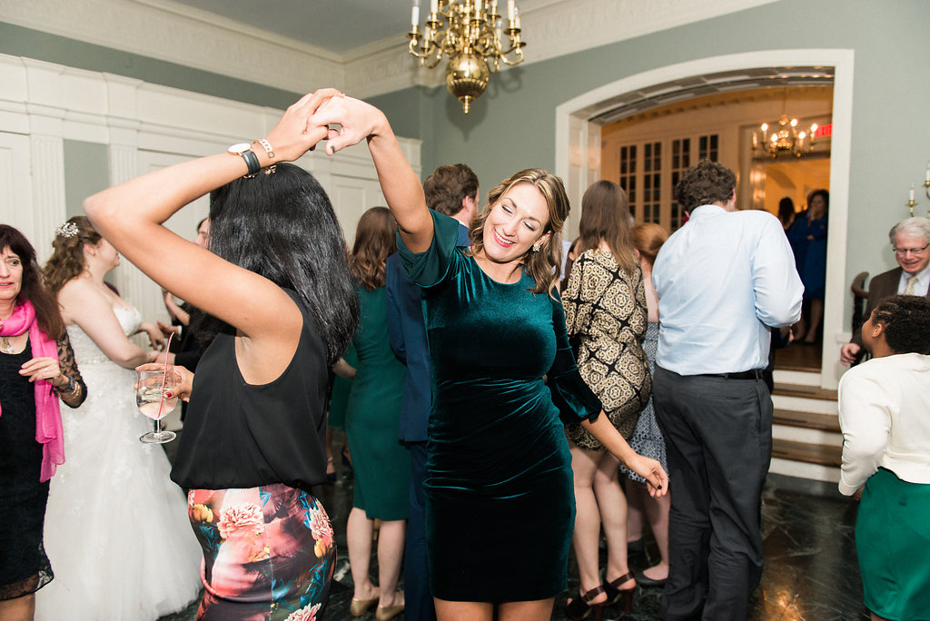 woman in green dress twirling another guest at wedding