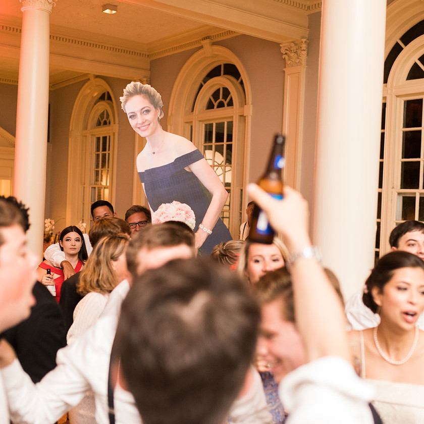 picture cutout of maid of honor held above wedding crowd while dancing