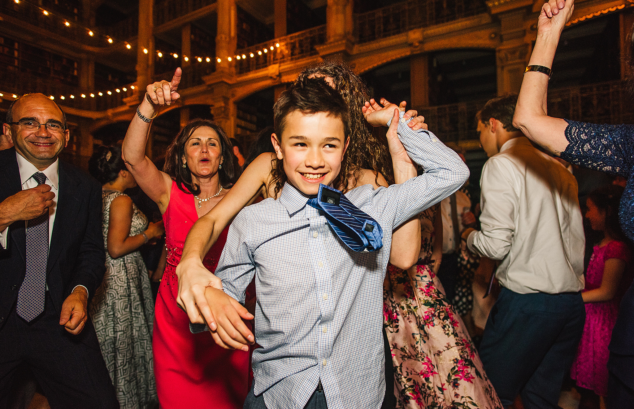 boy dances with family at wedding