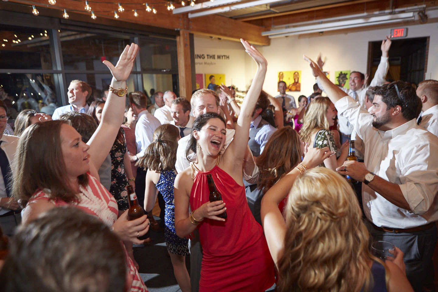wedding guests dance with hands up