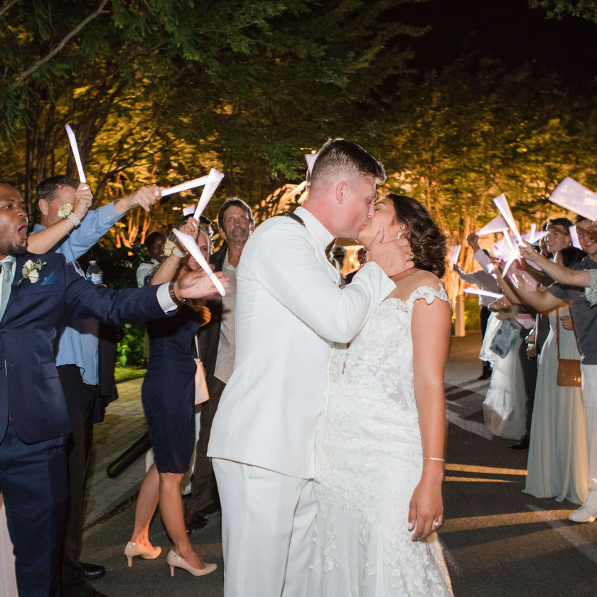 bride and groom kiss during wedding exit