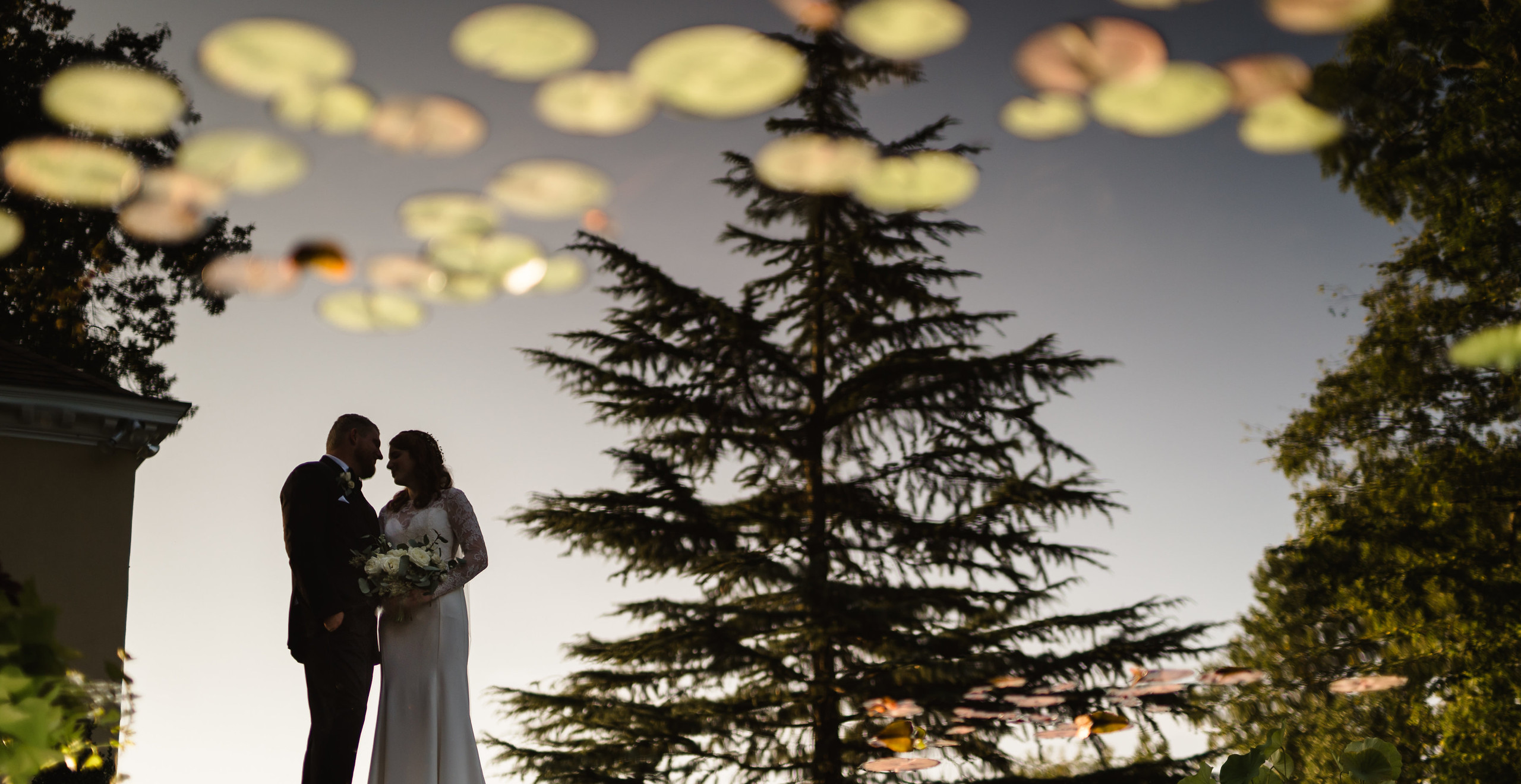 reflection in pond of bride and groom posing