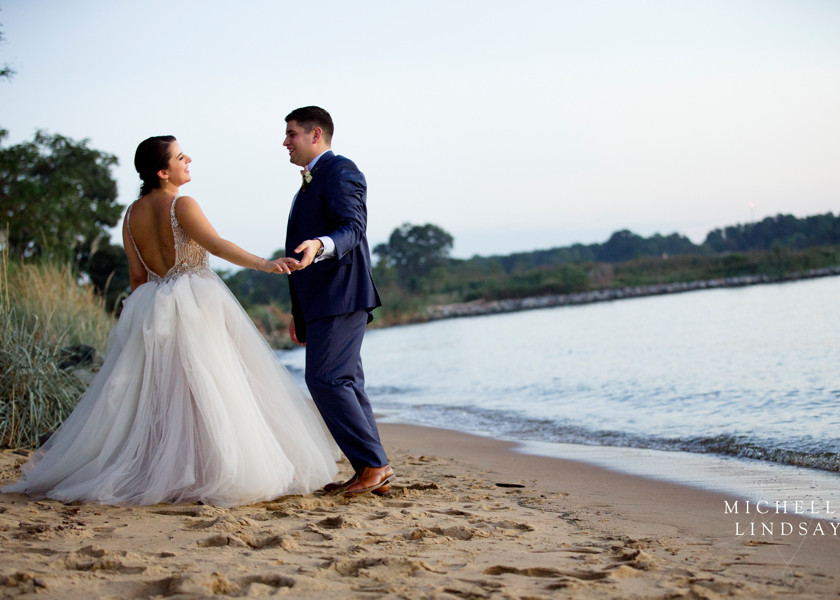 bride and groom stand on the beach