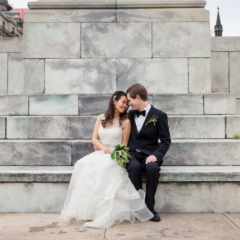 bride and groom sit by statue base