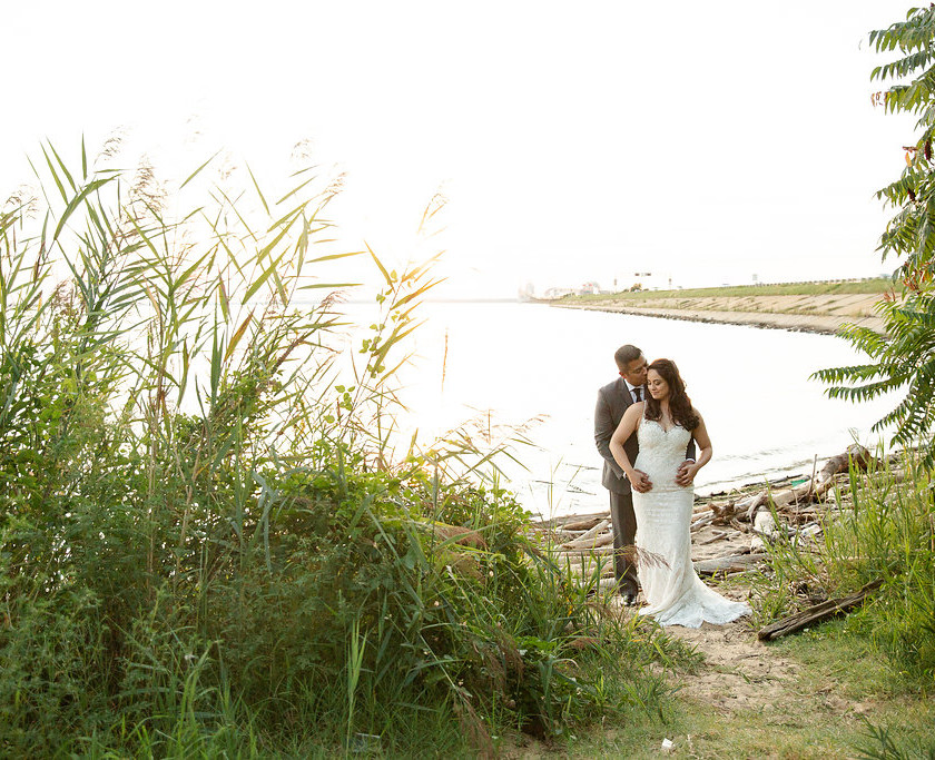bride and groom pose on small beach
