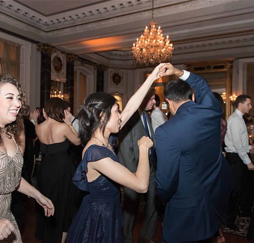 woman spins man while dancing at wedding