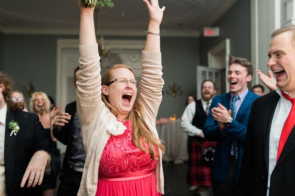 woman in red dress cheers during wedding
