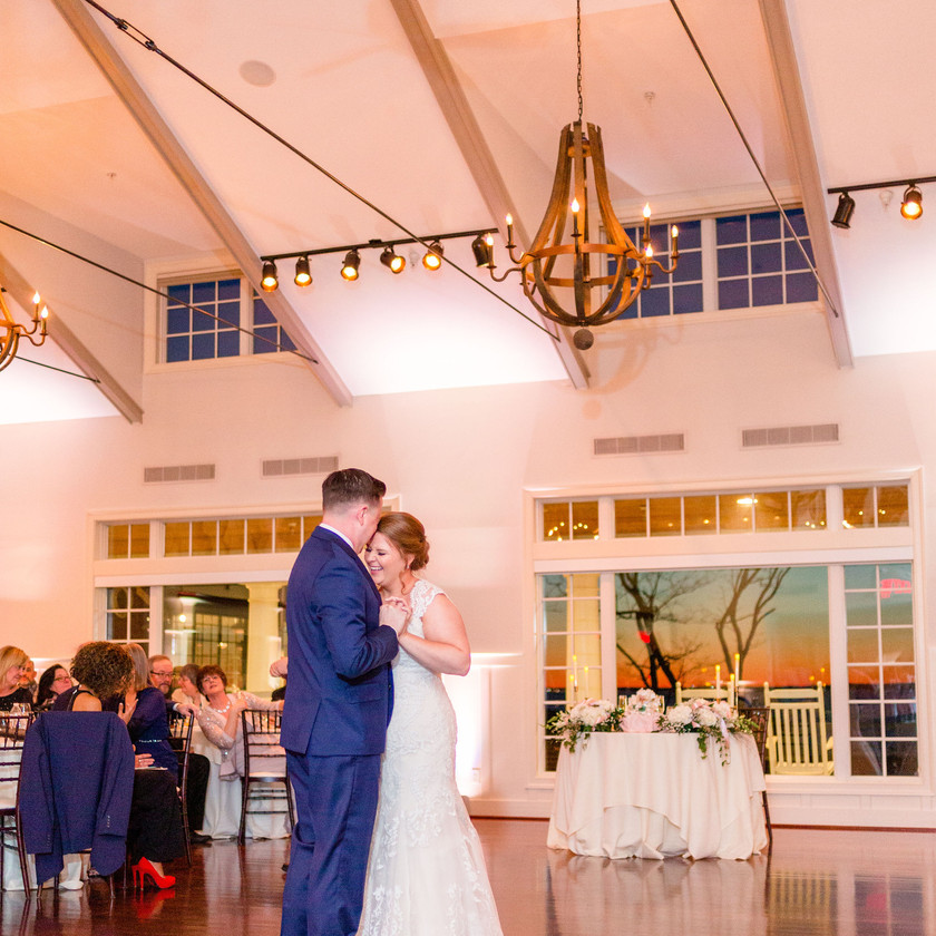bride and groom first dance while guests watch