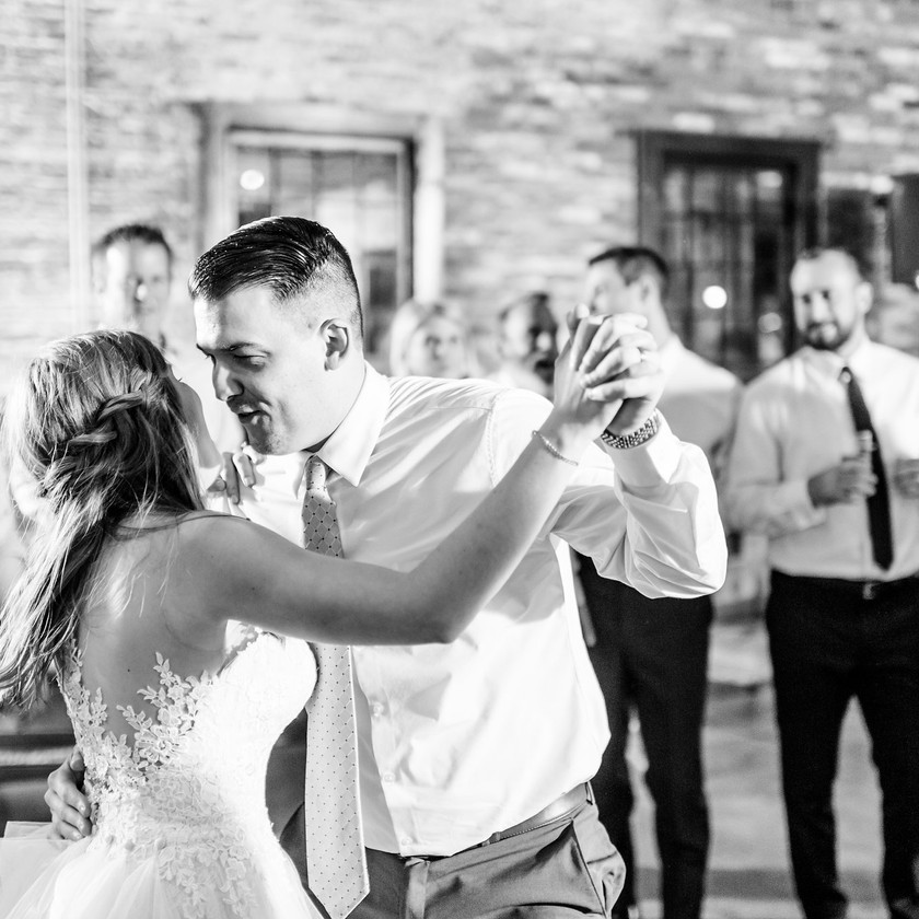 bride and groom dance surrounded by friends