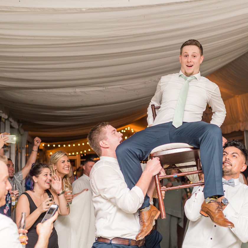 guys hold groom up in chair