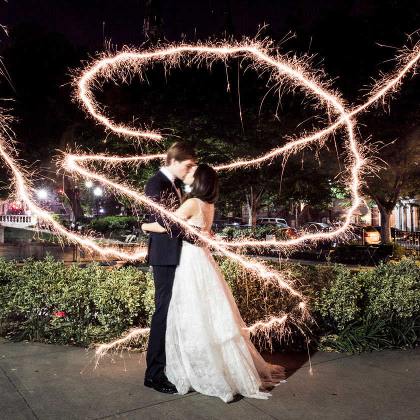 sparkler light trail goes around bride and groom as they kiss