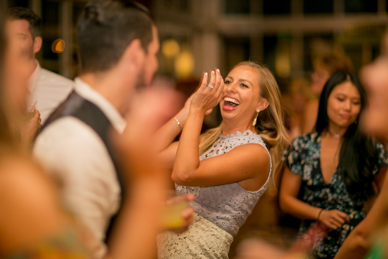 woman smiling and clapping while dancing at wedding