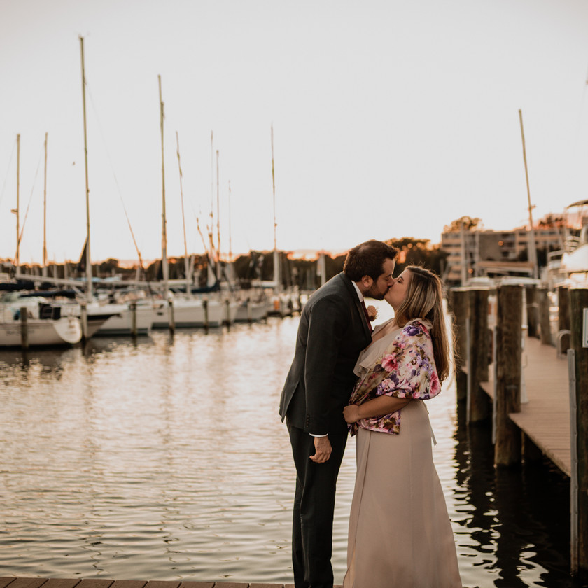 bride and groom kiss on boat dock