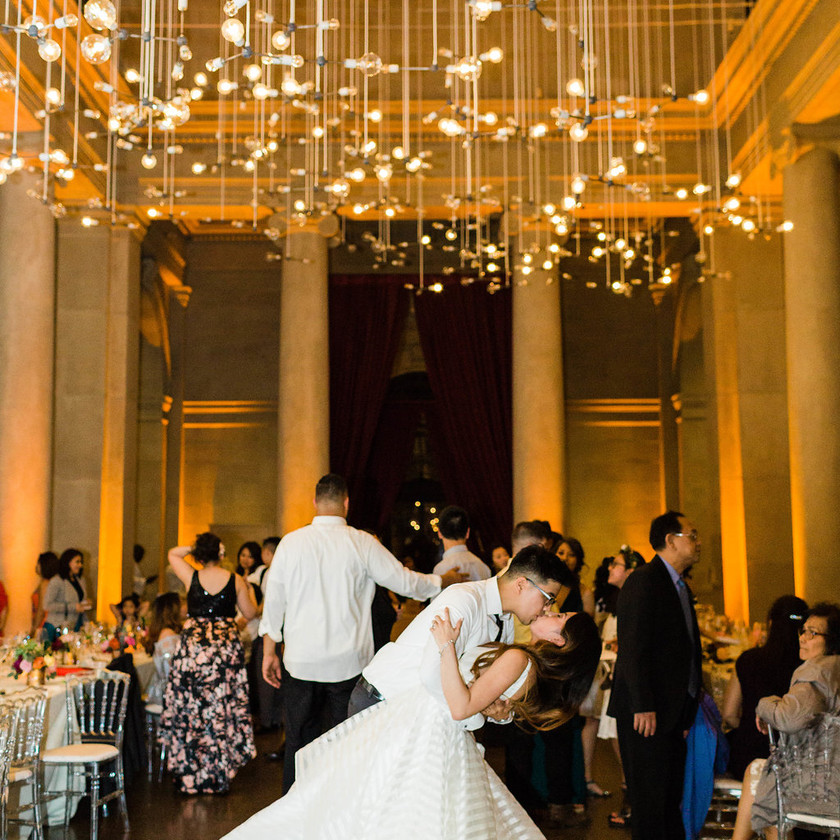 groom dips bride and kisses her on dance floor