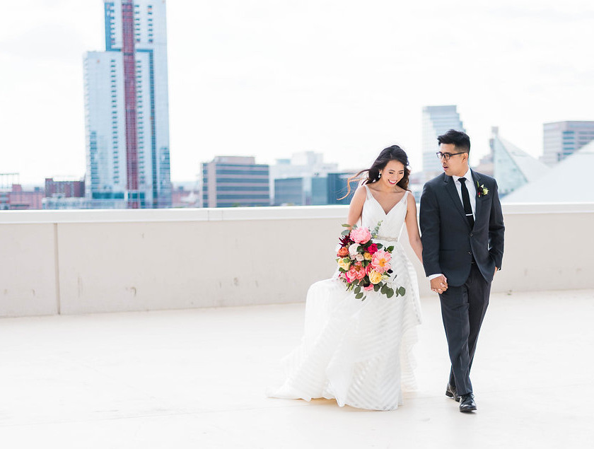 bride and groom walk on rooftop