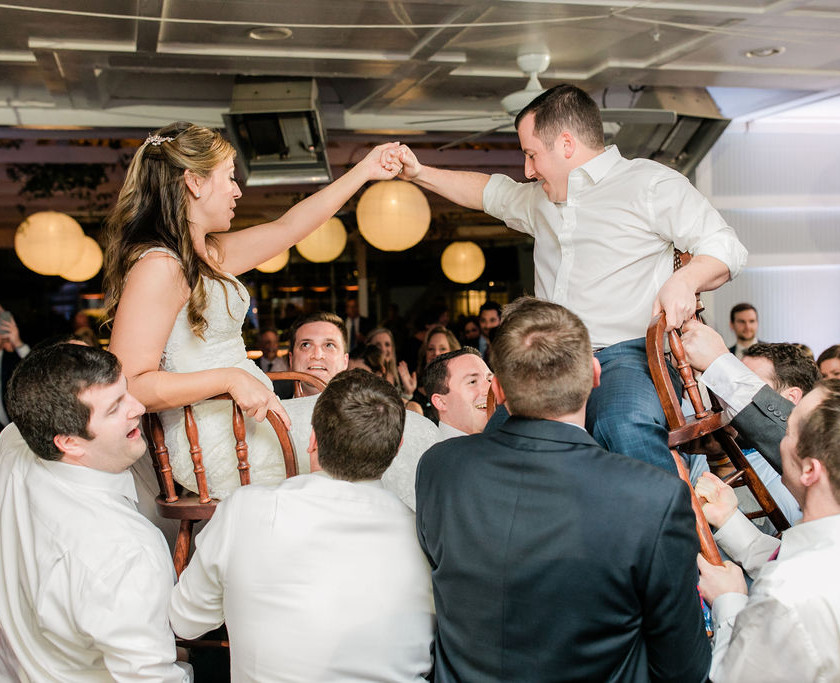 bride and groom holding hands while being held up in chairs