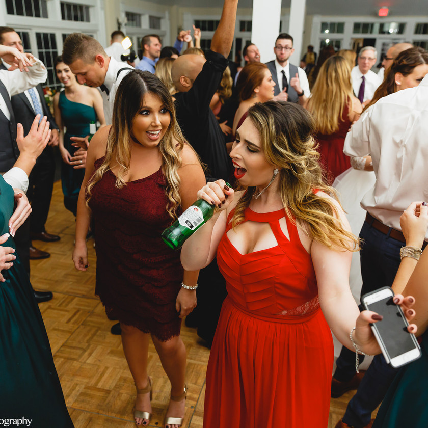 woman singing into beer bottle at wedding