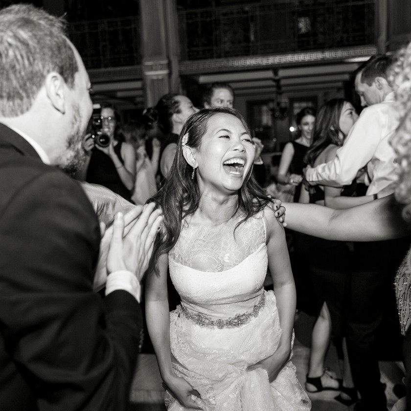 bride smiles while dancing with guests