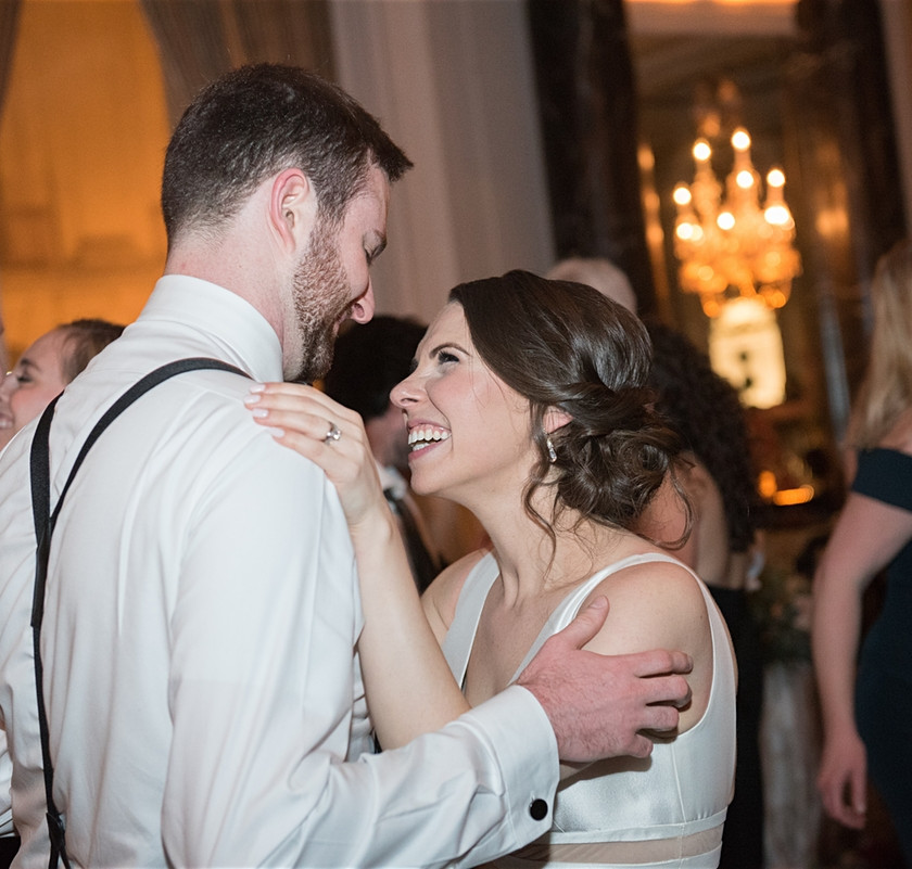 bride smiles at groom while dancing