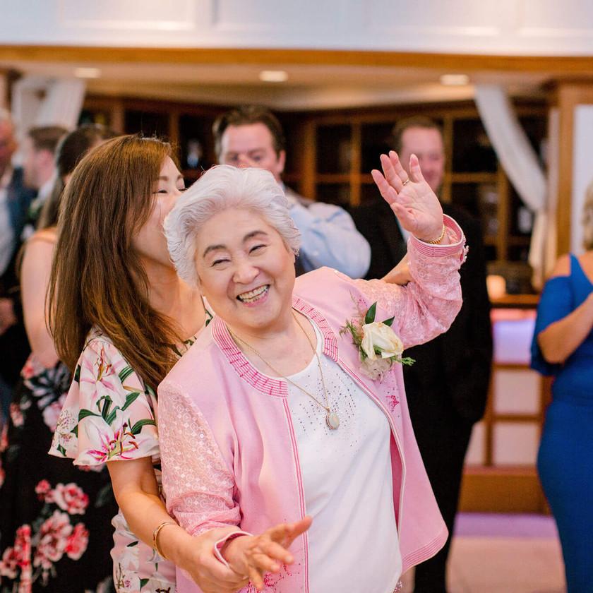older woman in pink jacket dancing at wedding