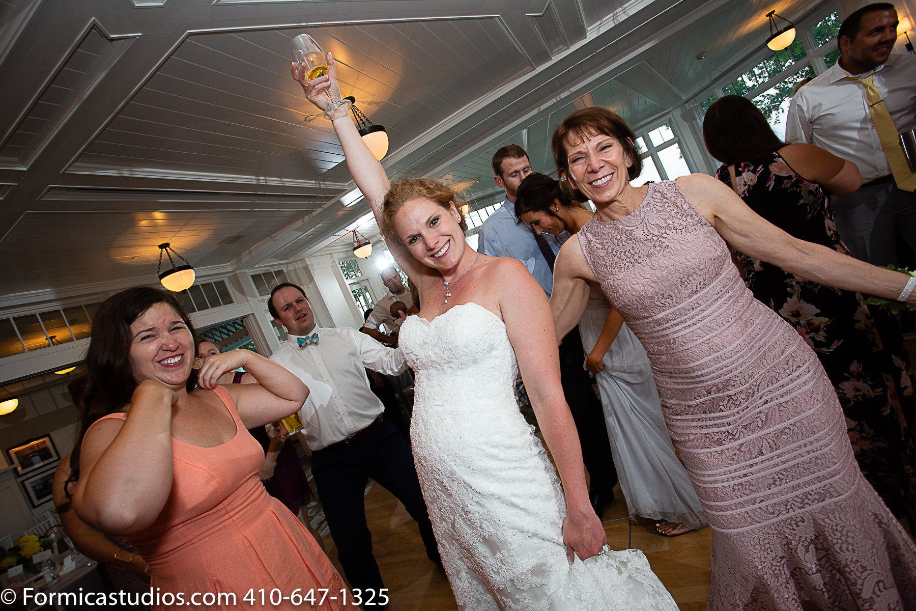 bride dancing with glass of wine in the air