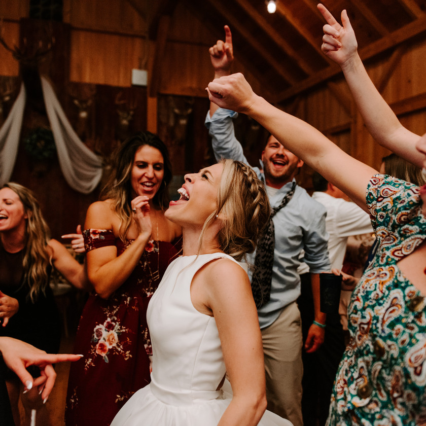 bride smiles while partying with guests
