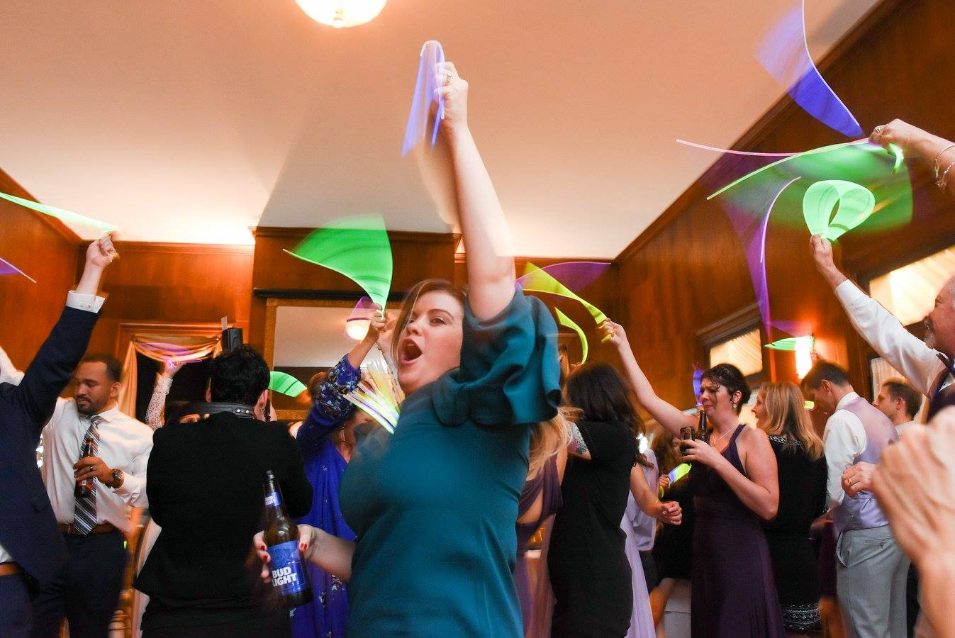 woman in turquoise dress dances with glow stick