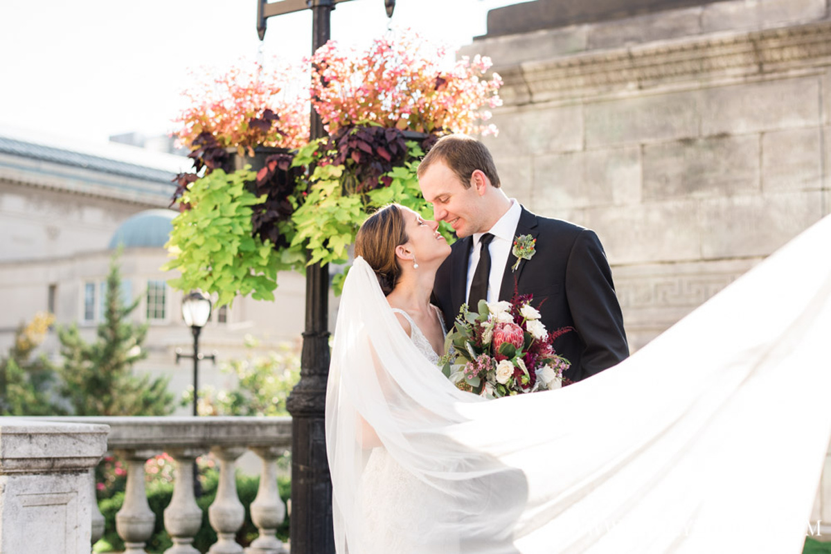 bride and groom about to kiss by statue outside