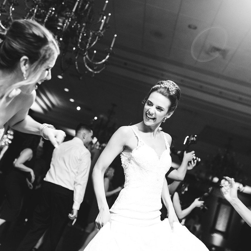 bride smiles at friend while dancing