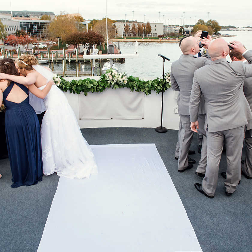 bride huddles with bridesmaids and groomsmen take drinks at ceremony