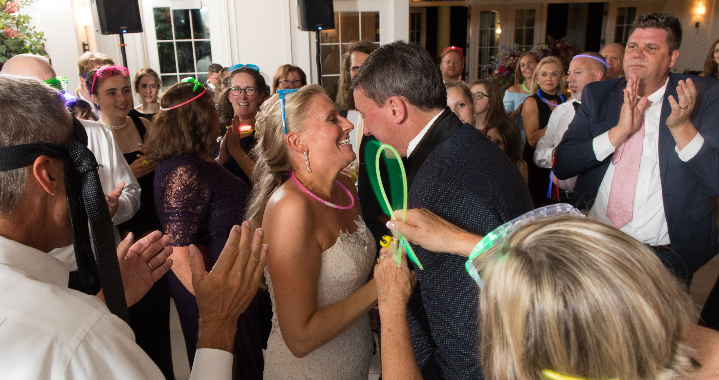 bride and groom dance with each other surrounded by friends