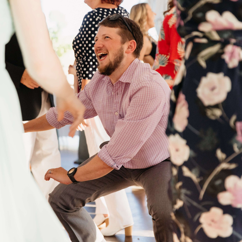 guy in red striped shirt gets low dancing at wedding